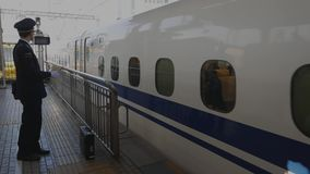 Shinkansen driver points and calls out the time and station name. stock video footage