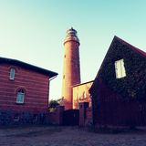 Shinning old lighthouse above houses before sunset. Tower illuminated with strong warning light Royalty Free Stock Image