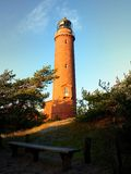 Shinning old lighthouse above houses before sunset. Tower illuminated with strong warning light Stock Images