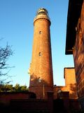 Shinning old lighthouse above houses before sunset. Tower illuminated with strong warning light Stock Photography