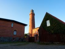 Shinning old lighthouse above houses before sunset. Tower illuminated with strong warning light Royalty Free Stock Images