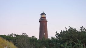 Shinning old lighthouse above pine forest before sunset. Tower illuminated with strong warning light. Lighthouse built from red br stock footage