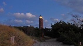 Shinning old lighthouse above pine forest before sunset. Tower illuminated with strong warning light. Lighthouse built from red br stock video footage