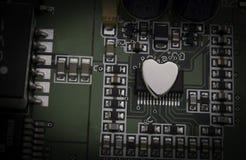 Shinny das Metallherz, das auf einer elektronischen Schaltung befestigt wird Lizenzfreies Stockfoto