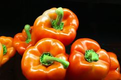 Shinny red caspian sweet bell peppers closeup against black backgound Royalty Free Stock Photography