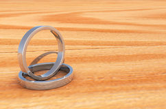 2 Shinny Silver Rings on Lite Wooden base Royalty Free Stock Photos