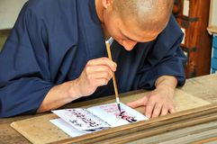 Shinshoku man writing a Shuin stamp for worshippers stock photography