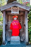 Shinto Altar. A shinto altar with a stone statue adorned with red clothes Royalty Free Stock Photography