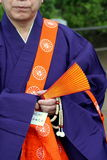 Shinto monk in Japan. With purple robes and orange sash and fan royalty free stock photography