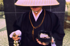 Shinto Monk Ringing Donation Bell in Tokyo Stock Photography