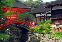 Shinto shrine with bridge. Red bridge and historical shrine buildngs at Shimogamo Shinto shrine in Kyoto, Japan stock photo