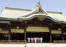 Shinto Temple With Priests. A traditional Shinto temple in Japan viewed from across a courtyard. Inside, a group of priests are lined up in the sanctuary for a stock images