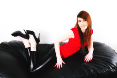 Shiny. Female model lying on a leather puffy (settee size) wearing shiny leggings and a bright red top Royalty Free Stock Photos