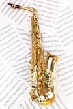 Shiny alto saxophone in full size on musical notes. Shiny golden alto saxophone in full size on the musical notes background with standard scales exercises Stock Photos