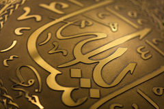 Shiny arabic script relief. Golden look islamic relief on metal plate Stock Photos