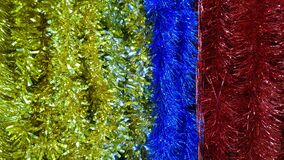 Shiny background of blue, golden and red Classic Tinsel Garland. Traditional Christmas decorations. Xmas collection. Happy New Yea