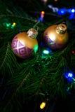 Shiny balls on a Christmas tree among colorful lights. stock photos