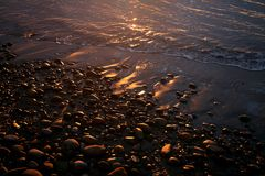 Shiny beach pebbles at sunrise Royalty Free Stock Photos