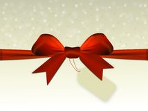 Shiny beige background with red bow with label Royalty Free Stock Photography