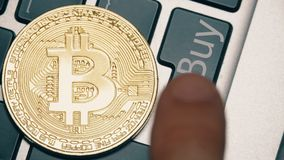 Shiny bitcoin on the computer keyboard and the Buy button being pressed Stock Images