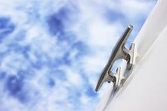 Shiny bitt on yacht board. Blue cloudy sky as background. No rope. Closeup Stock Image