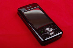 Shiny black PDA on red. Stock Photography