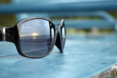 Shiny Black Sunglasses on Large Blue Wood Chair Stock Photo