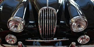 Shiny black vintage sport car. Front lamps with grill closeup Stock Images