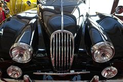 Shiny black vintage sport car. Front lamps with grill closeup Royalty Free Stock Images