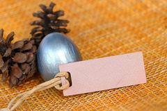 Shiny blue easter egg with blank paper tag Royalty Free Stock Photo