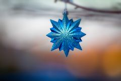 Shiny blue hanging Christmas Tree Ornaments at sunset Royalty Free Stock Photo