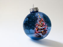 Shiny Blue Holiday Ornament Reflects Brightly Lit Colorful Christmas Tree. This shiny blue Christmas ball ornament reflects a brightly lit Christmas Tree and Stock Photography