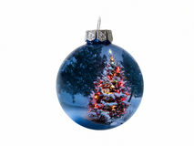 Shiny Blue Holiday Ornament Reflects Brightly Lit Colorful Christmas Tree. This shiny blue Christmas ball ornament reflects a brightly lit Christmas Tree and Royalty Free Stock Photo