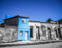 Blue house under blue sky in cuba. Shiny blue house surrounded by monochrome houses under a blue sky in camaguey, cuba Royalty Free Stock Photography