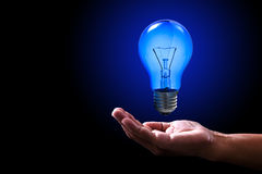Shiny blue light bulb and power human hand. Bright blue light bulb floating above right human hand with black backdrop Stock Photo