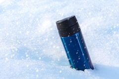 Shiny blue metal thermo mug standing in the sparkling snow with falling snowflakes. Copy space stock photos