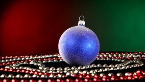 Shiny blue toy for Christmas or New Year and beads. Shiny blue toy for Christmas tree for decoration Christmas or New Year and red and white beads, rotation, on stock video footage