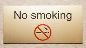 Shiny brass plate restricting smoking. On hotel floor Stock Image