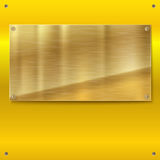 Shiny brushed metal gold, yellow plate with screws. Royalty Free Stock Photos