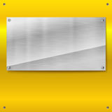 Shiny brushed metal plate with screws. Royalty Free Stock Images