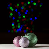 Shiny christmas balls on the black background. With colorful bokeh Stock Images