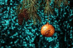 Shiny Christmas gold ball hanging on pine branches with festive background Stock Photos