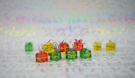 Shiny Christmas photography picture with miniture glass red green yellow christmas present tree decorations on wrapping paper Royalty Free Stock Images