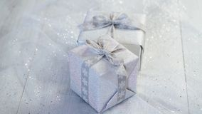 Shiny christmas table decoration with two silver presents. With ribbon stock footage