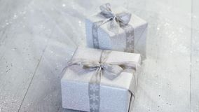 Shiny christmas table decoration with two silver presents. With ribbon stock video