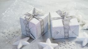 Shiny christmas table decoration with two silver presents with snowflakes and stars. Shiny christmas table decoration with two silver presents with snowflakes stock footage