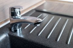 Shiny chrome faucet in a brand new kitchen. With a granite sink Royalty Free Stock Photo