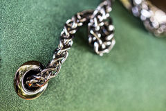 Shiny chrome metal rivet and chain in beautiful green leather fa. Shiny chrome metal rivet and steel chain in beautiful green leather fabric surface as fashion stock photos
