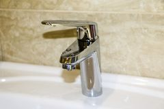 Shiny chrome-plated faucet in  bathroom, with water drops stock photo