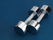Shiny Chromed Dumbbells. Shiny chrome plated fitness dumbbells isolated on blue background Stock Photography